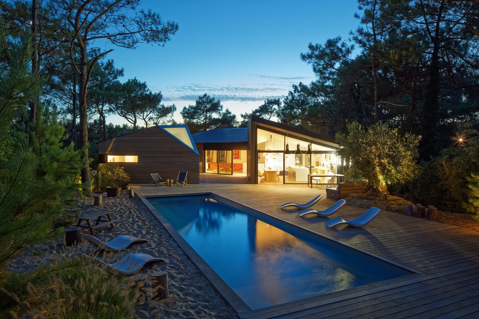 Outdoor, Back Yard, Wood Patio, Porch, Deck, Trees, Swimming Pools, Tubs, Shower, Hardscapes, and Large Patio, Porch, Deck At sunset, the holiday home glows like a shining lantern set within the forest.   Photo 7 of 13 in Multiple Modern Cabins Make Up This French Holiday Home