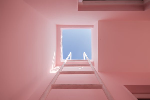 A built-in ladder provides access to the roof deck.  The blue skies contrast with the light pink walls, creating a pastel composition of solid and void.