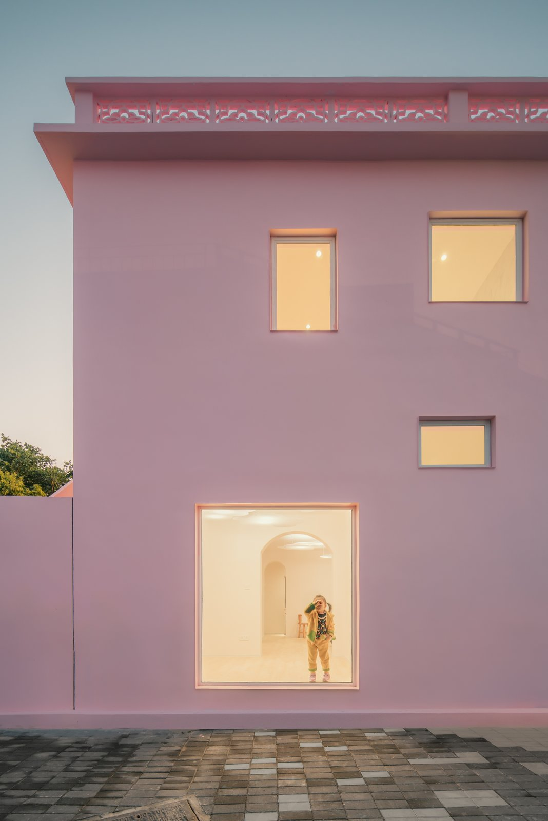 Exterior, Flat RoofLine, House Building Type, and Stucco Siding Material Large windows connect occupants to the exterior courtyard and surroundings.   Photo 11 of 17 in These Pink and Blue Homes Use Gender as a Metaphor For Urban Revitalization