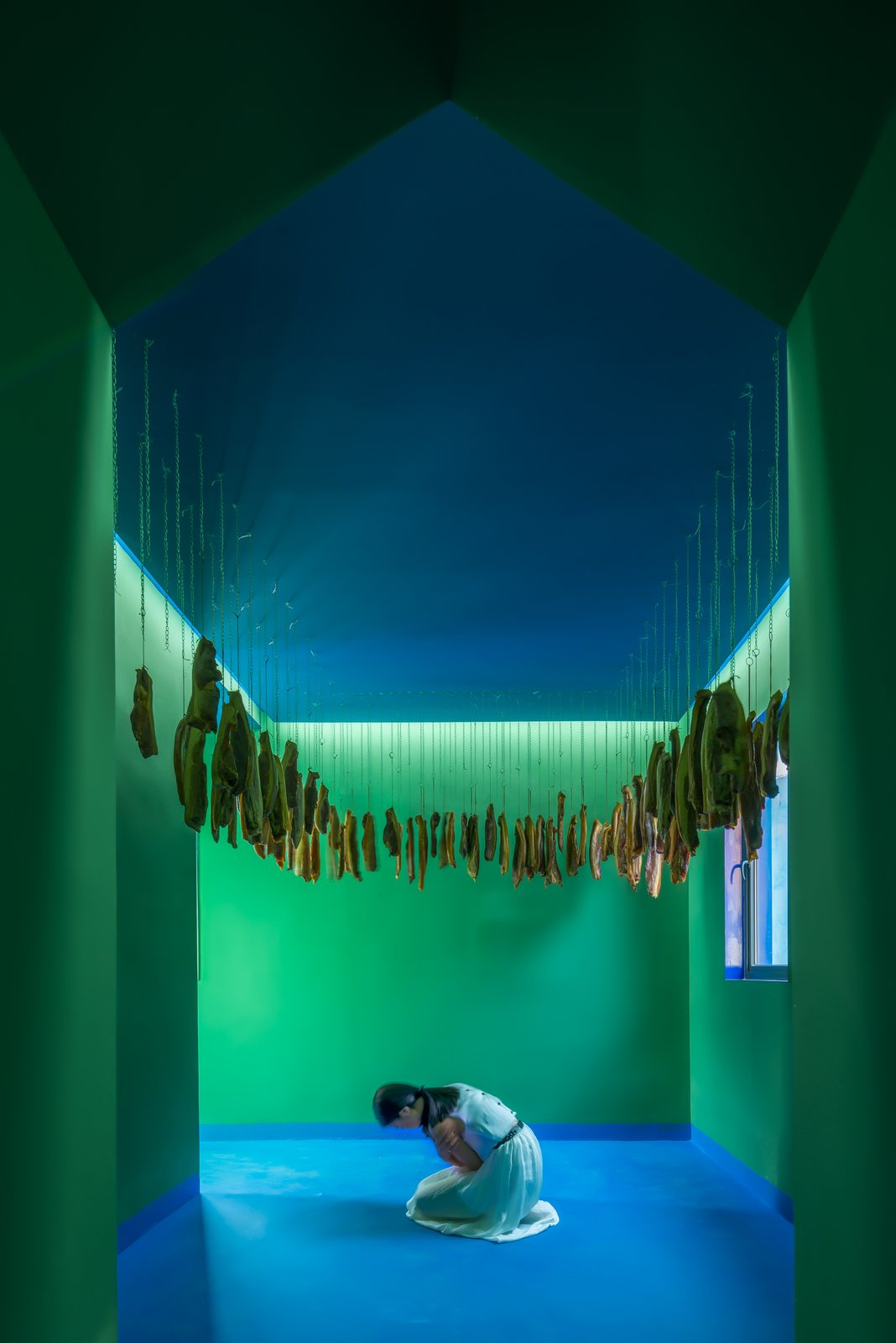 Living Room Bacon, a preserved creation, is hung from the ceiling of the first installation.  The green walls continue a masculine motif while the blue continues through the ceiling, floor, and windows.   Photo 5 of 17 in These Pink and Blue Homes Use Gender as a Metaphor For Urban Revitalization