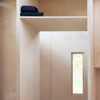 All storage and shelving is meticulously integrated into the overall design.  A shelf above the bath provides storage for hiking packs.