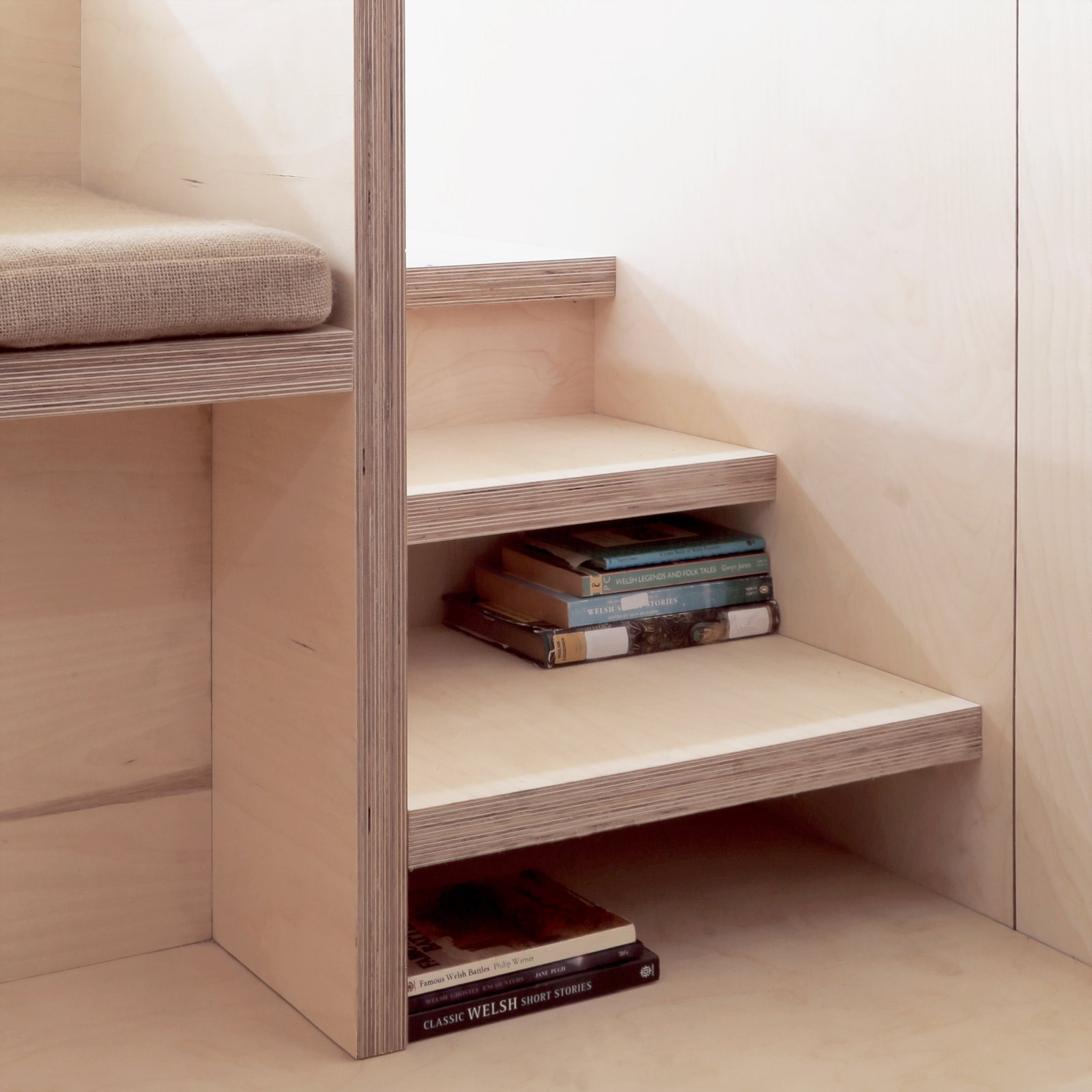 Storage Room, Shelves Storage Type, and Under Stairs Storage Type Stairs leading up to the platform bed double as storage for books.   Photos from This Small Slate Cabin Rental is the Ultimate Outdoor Oasis