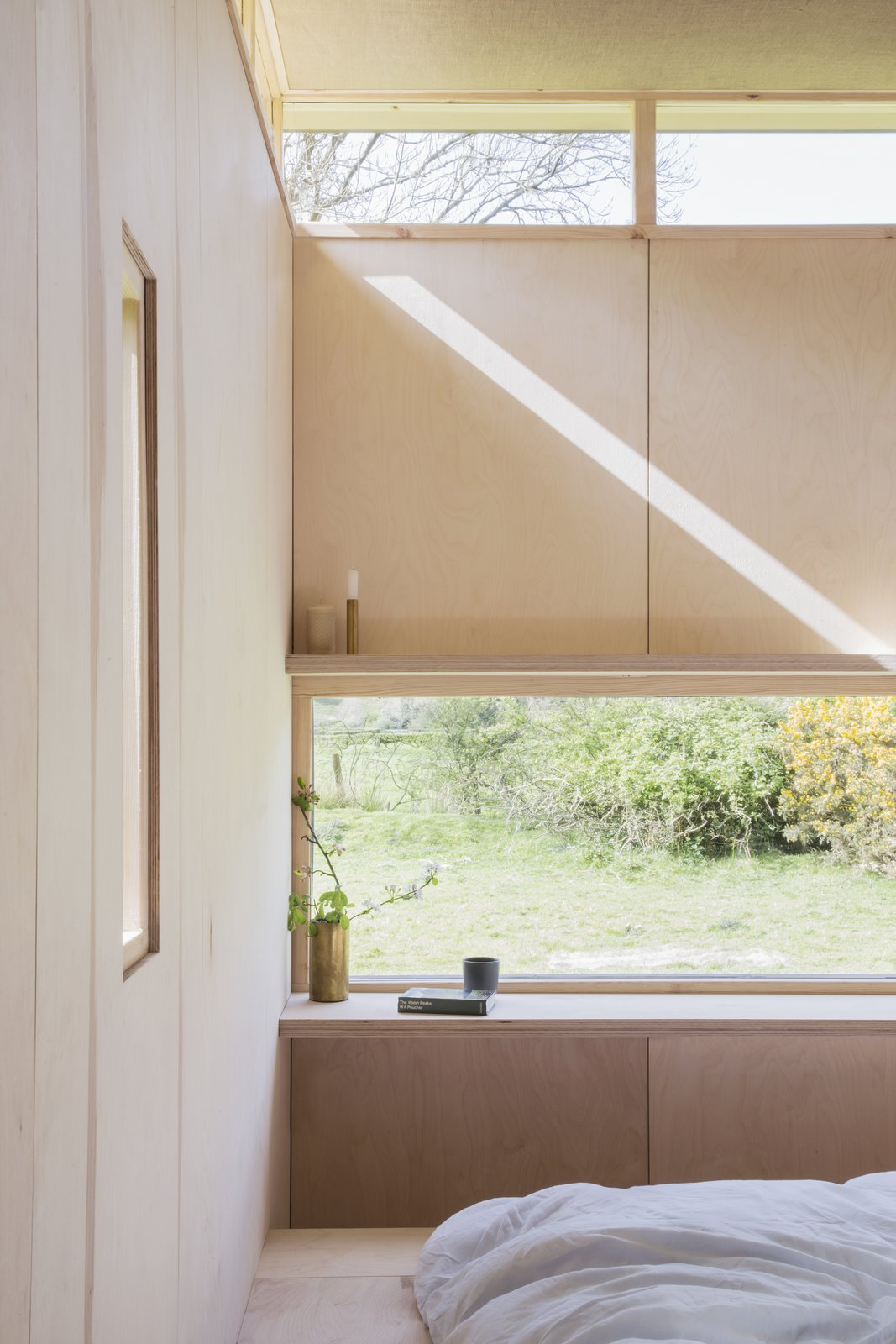 Bedroom, Bed, Shelves, Light Hardwood Floor, and Storage A long window frames panoramic views of the setting beyond.   Photo 8 of 11 in This Small Slate Cabin Rental is the Ultimate Outdoor Oasis