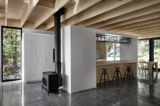 The kitchen is framed by two white walls which link  to the adjoining spaces.