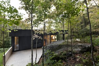 The home appears as if it is carved into the mountainside, one with the trees and rock formations.