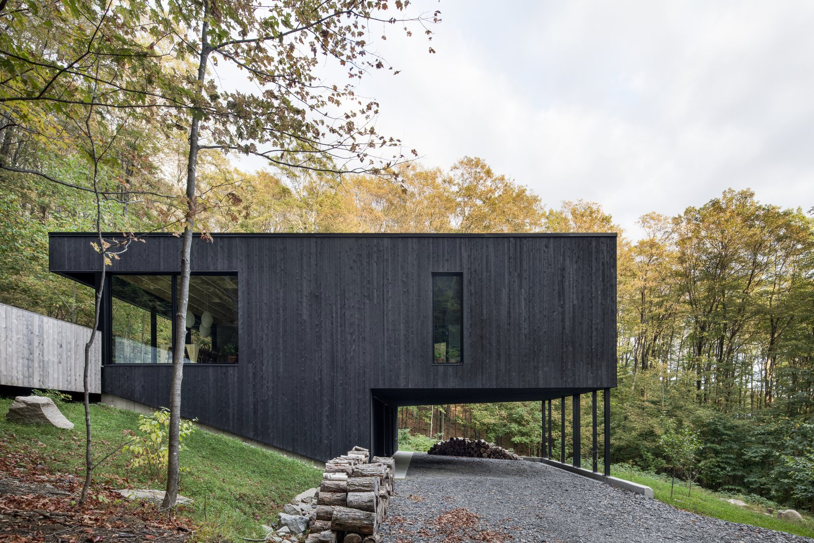 Exterior, House Building Type, Flat RoofLine, and Wood Siding Material Supported on thin columns, the main volume hovers above the graveled entry, reaching out into the surroundings.   Best Photos from This Wood-Clad Home Is Built Into a Serene Mountain Slope