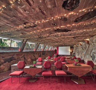 The Cabaret Theater, used for music and theater, displays the thickness of the exterior walls with buttressing structural supports extending to the roof.  Bold red chairs and lush red carpet match the warm, dessert hue.