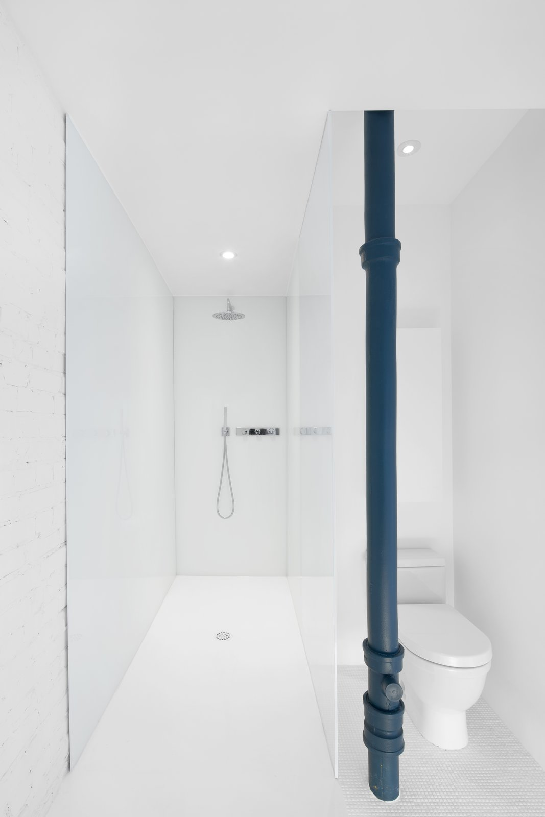 Bath Room, Open Shower, Recessed Lighting, and Two Piece Toilet White laminated glass creates the shower surround.  A blue painted pipe adds a singular color element to the bath space.   Photo 9 of 12 in A 1910 Apartment Transforms Into an Open, Radiant Loft