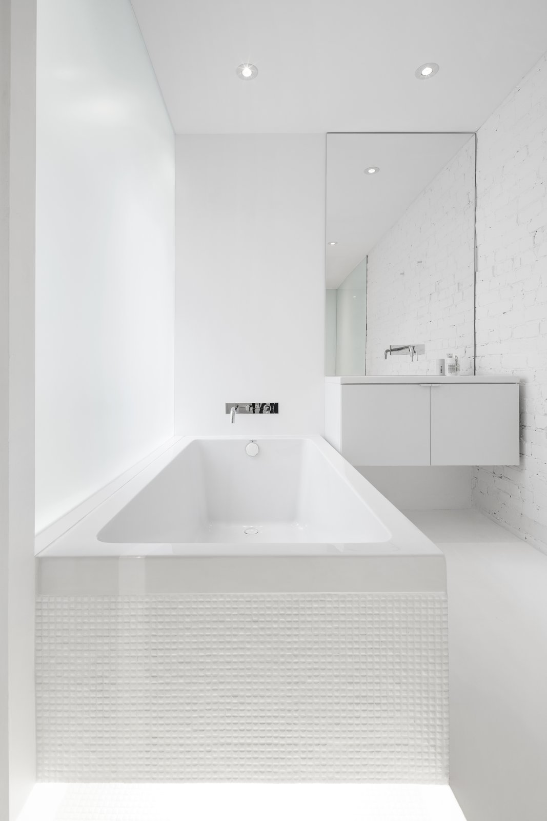Bath, Soaking, Wall Mount, Recessed, and Drop In An opaque glass wall which extends the length of the tub, allows filtered light into the bath space.  All white elements allow the light to reflect, creating a bright interior.   Best Bath Recessed Drop In Photos from A 1910 Apartment Transforms Into an Open, Radiant Loft