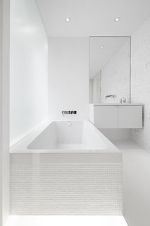 An opaque glass wall which extends the length of the tub, allows filtered light into the bath space.  All white elements allow the light to reflect, creating a bright interior.