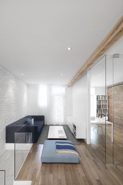A lounge space, decorated with dark and light blue hues, sits directly atop the entry stairs.  A white painted brick wall provides an idea backdrop which extends between spaces.