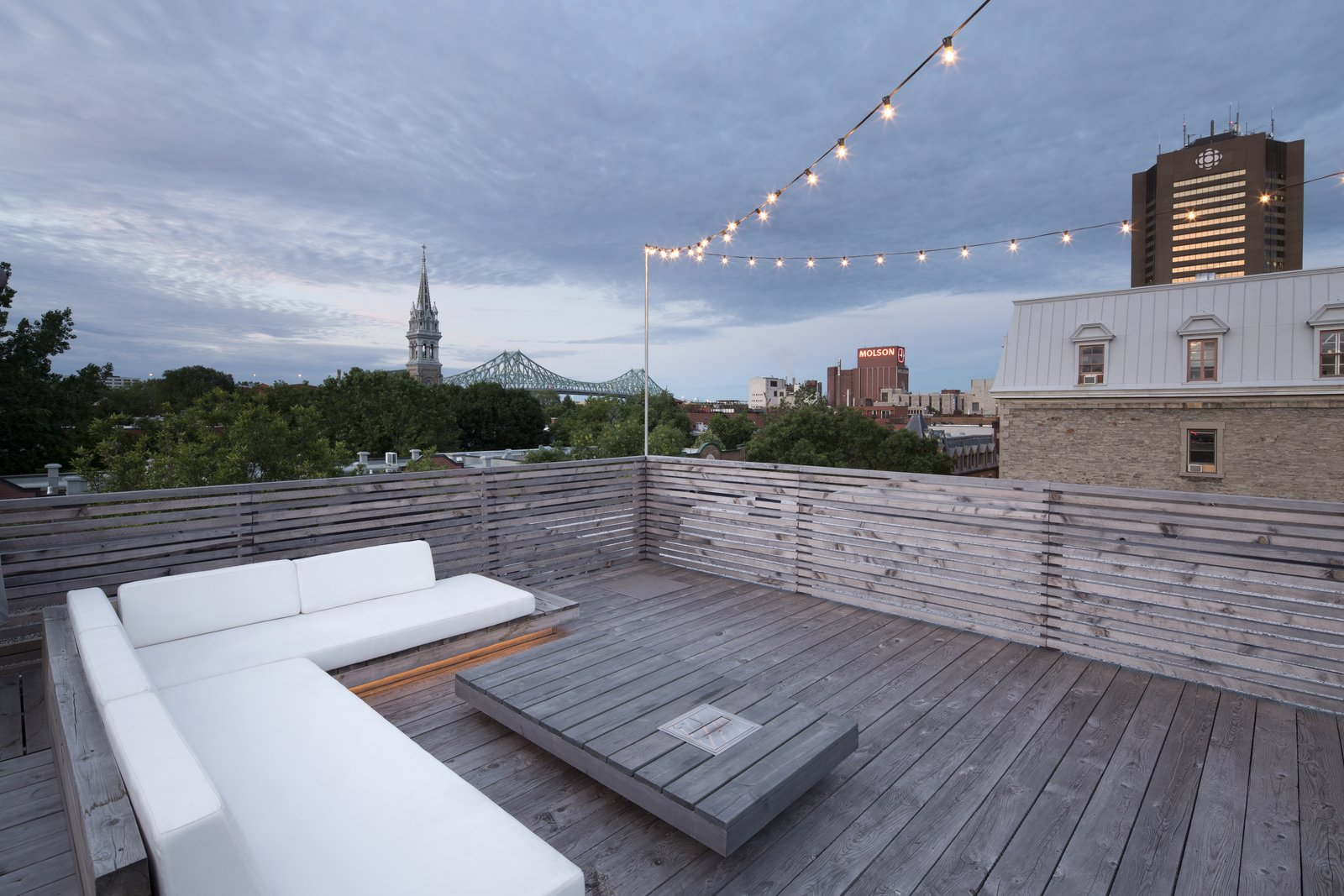 Outdoor, Rooftop, Wood, Wood, Horizontal, and Hanging The wood deck roof terrace, complete with ample lounge seating, provides astounding views of the city beyond.   Best Outdoor Hanging Photos from A 1910 Apartment Transforms Into an Open, Radiant Loft