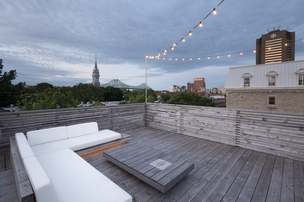 The wood deck roof terrace, complete with ample lounge seating, provides astounding views of the city beyond.