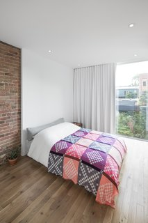 In the bedroom, full height glazing allows natural light to fall deep into the apartment.  Elegant, white curtains provide privacy as needed, well matching the surrounding wall colors.