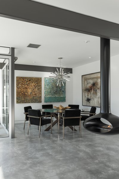 Modern furnishings, a decorative metallic pendant, and colorful artwork decorate the dining space.