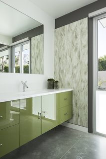 Glossy green cabinets, textured wall coverings, and polished concrete floors in desert hues decorate one of the guest baths.