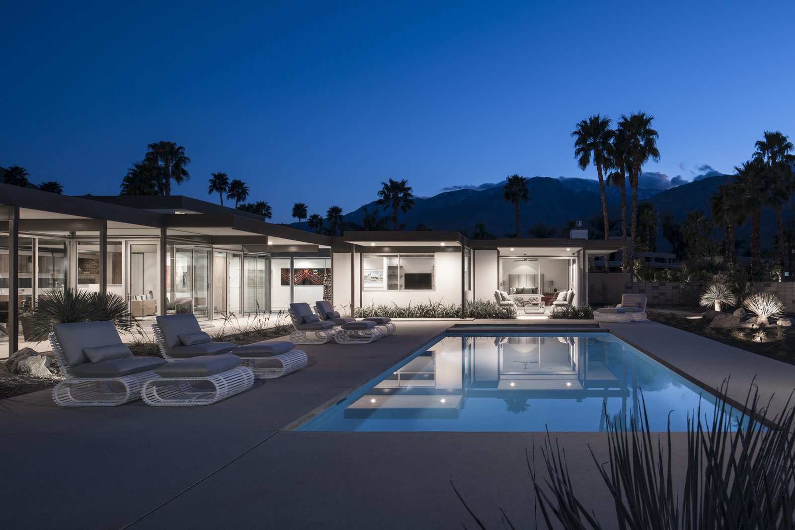 Outdoor, Shrubs, Swimming, Trees, Large, Landscape, Boulders, Back Yard, Desert, and Concrete At dusk, the light-colored home glows like a lantern in the desert sky.  Best Outdoor Desert Swimming Photos from The Last Donald Wexler–Designed Home Ever Built Asks $2.65M