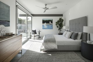 One of the three bedrooms emotes a comfortable, relaxing feel with plush textiles and bedding. Again, full-height glazing brings the outdoor sunshine in.
