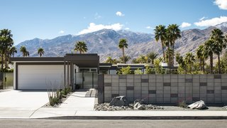 A steel-framed canopy leads directly to the front entry of the dwelling.  A concrete block fence provides privacy from the surrounding neighborhood. Drought-tolerant landscaping dots the landscape.