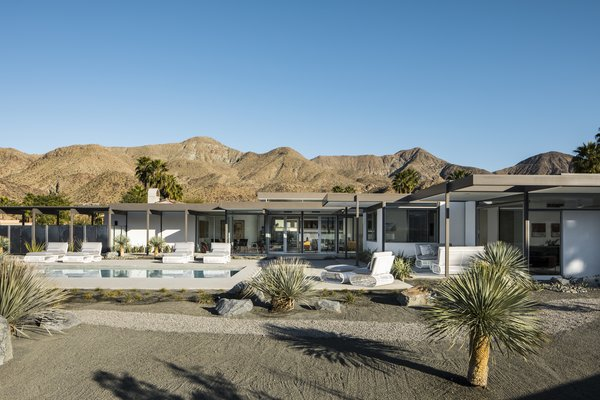 Mountainous terrain surrounds the modern, desert home.  Horizontal roof planes extend outward, connected the home to the desert land.