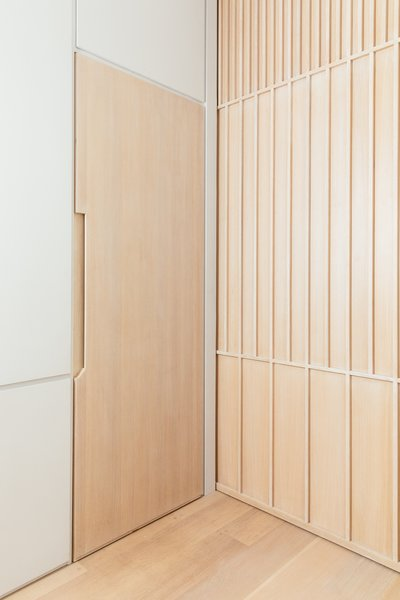 Integrated door pulls omit the need for additional hardware.  The wood pocket door is a geometric pattern of linear wood details.
