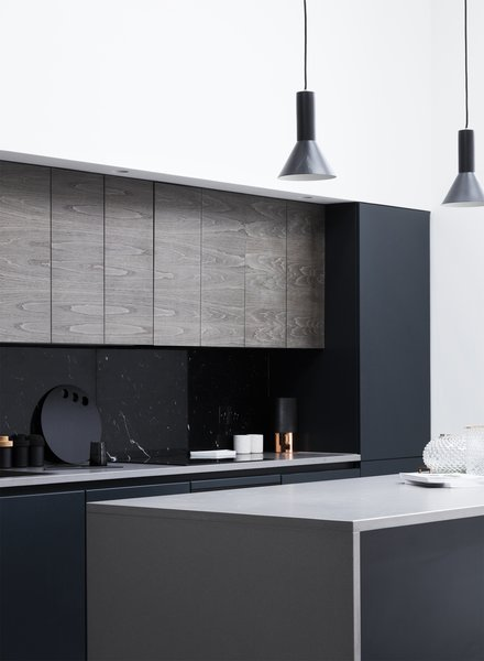 A black marble back splashed and matched oak veneer door fronts contrast with the white walls and light wood panels throughout the home.  Flat panel cabinets add an extra modern flair.