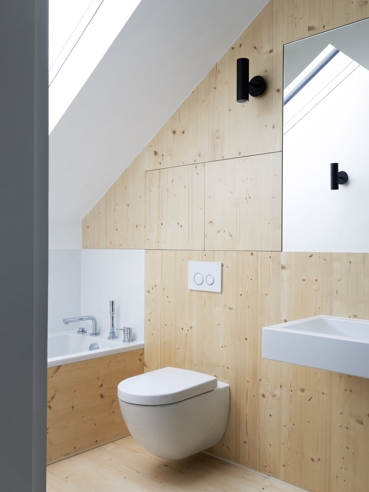 Bath, Light Hardwood, Wall Mount, One Piece, Wall, and Drop In Wooden panels provide a contrast of warmth against the white walls and fixtures.   Bath Drop In Wall Wall Mount Photos from A Forgotten Warehouse Is Reborn Into a Light-Filled London Home
