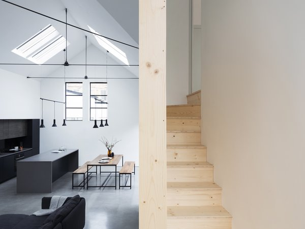 The wooden staircase winds its way between the main living space and the sleeping spaces above.