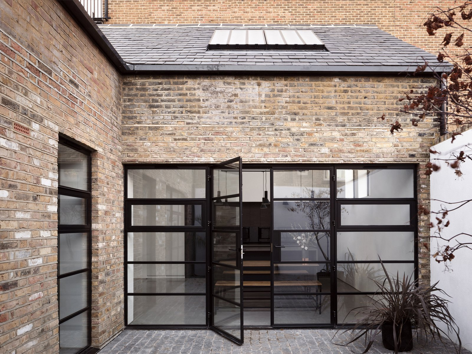 Doors, Exterior, Swing Door Type, and Metal Operable doors and windows and doors provide fresh air ventilation off a newly created interior courtyard space.   Photo 2 of 12 in A Forgotten Warehouse Is Reborn Into a Light-Filled London Home