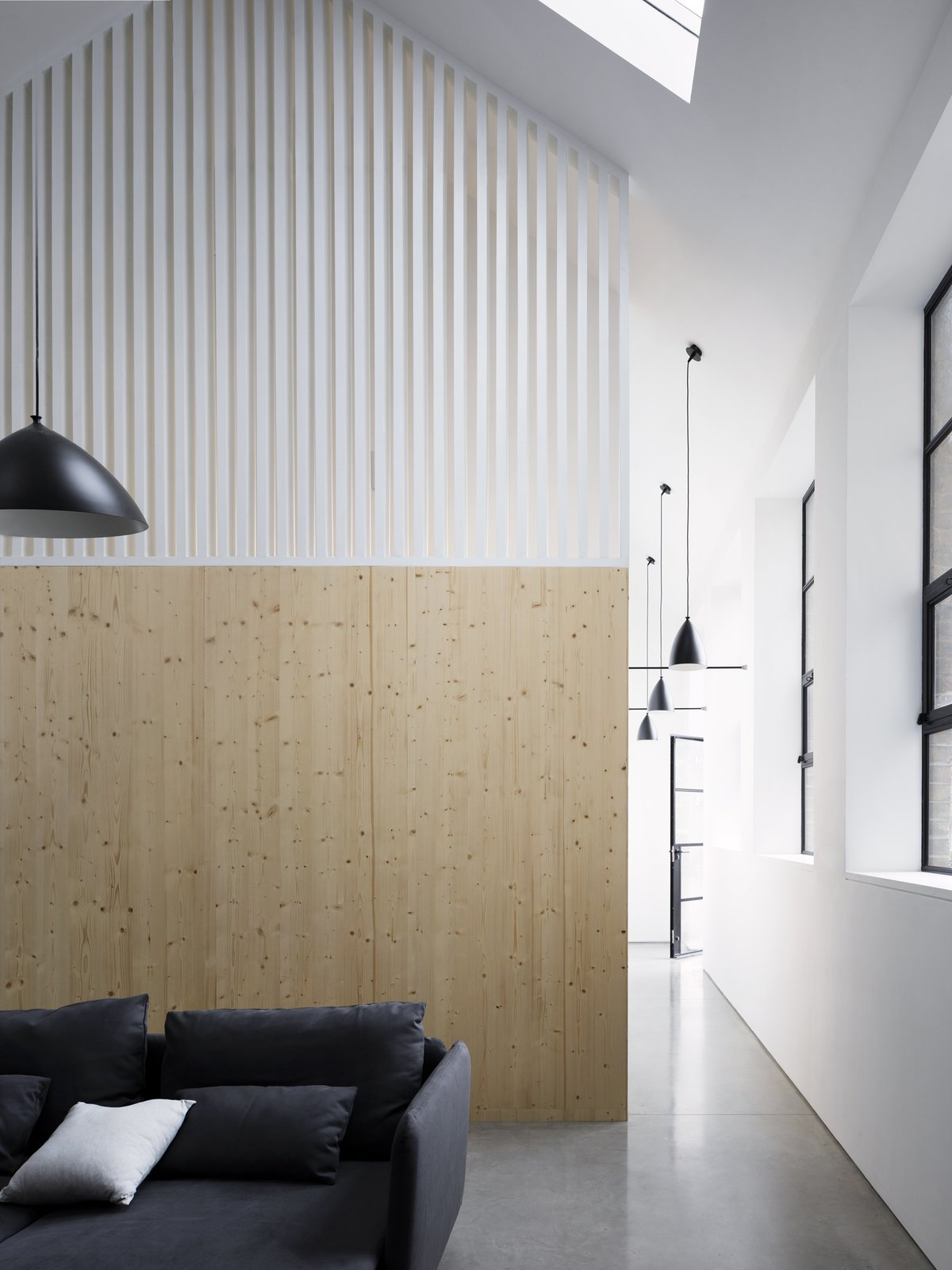 Living Room, Concrete Floor, Pendant Lighting, and Sectional The staircase is hidden between wood paneled walls adorned with white, wooden slats, allowing light to filter into the stairway.   Photo 8 of 12 in A Forgotten Warehouse Is Reborn Into a Light-Filled London Home