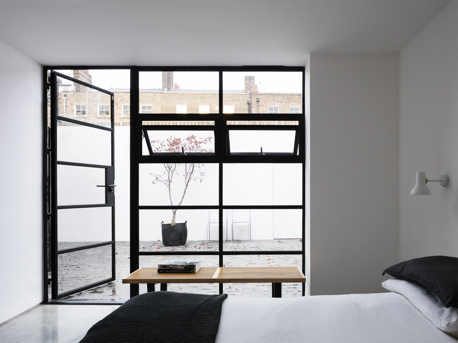 Bedroom, Bench, Concrete Floor, Wall Lighting, and Bed A interior courtyard is accessible from the bedroom, providing an unexpected secluded oasis right in the heart of an urban setting.   Photo 4 of 12 in A Forgotten Warehouse Is Reborn Into a Light-Filled London Home