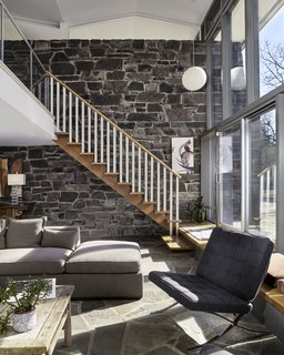An upper mezzanine overlooks the great room. Full-height glazing provides views of the surrounding natural setting. The stone wall appears to seamlessly slide from inside to outside. A original, signed Isamu Noguchi paper lamp hangs above the stair.