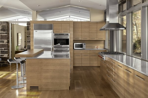 The kitchen cabinets were updated in a pecan finish, in roughly the original layout. Originally, the kitchen had a wall separating it from the rest of the room, and two sliding doors that could be opened. This wall was removed to open the kitchen to the living space.