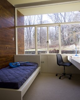 Wood siding extends from the interior of the children's bedroom to the exterior. A built-in desk sits just below the window sill. Large windows provide a direct connection to the outdoors.