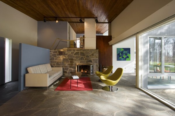 Flagstone flooring flows between the open living spaces. A stone fireplace anchors the main living space, while cedar wood decking extends between spaces above. A blue entry partition adds a pop of modern color.