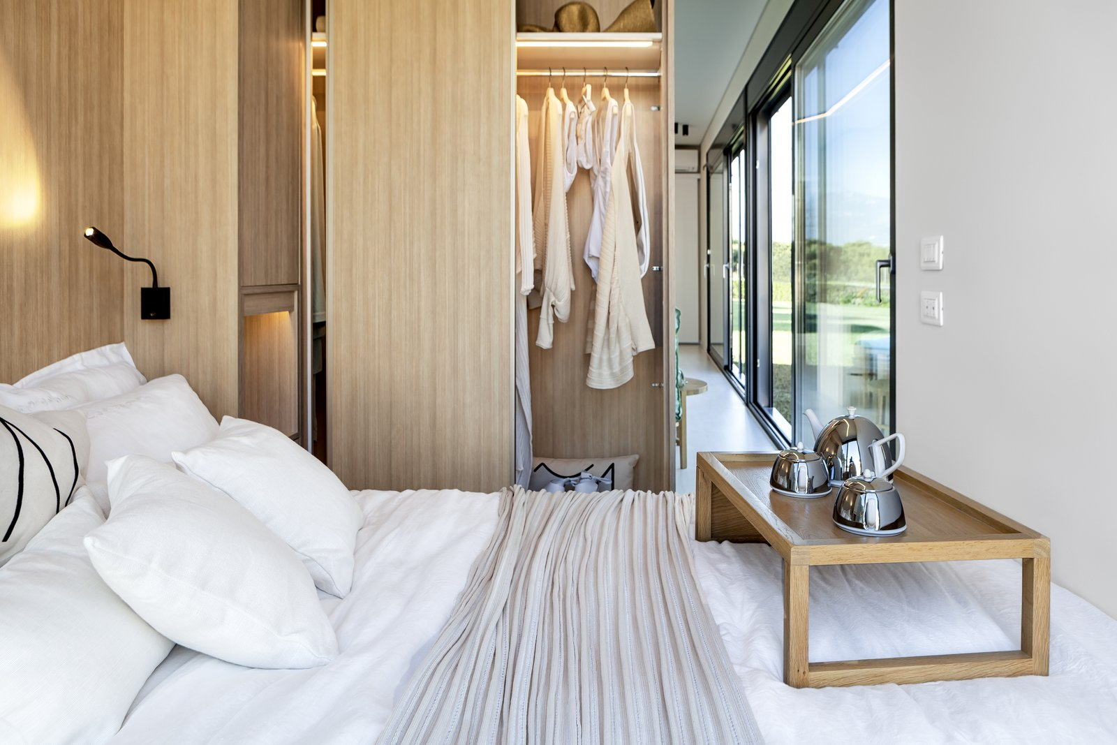 Bedroom, Storage, Wardrobe, Light Hardwood Floor, Wall Lighting, and Bed Built-in closets create a wall between the sleeping quarters and living spaces, allowing for more storage space.    Photo 7 of 10 in This Eco-Friendly Shipping Container Is the Ultimate Nomadic Dwelling