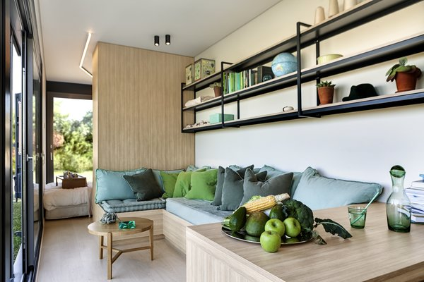 Colorful teal and green cushions decorate the built-in wood furniture. Simple open shelves extend along the living space, providing additional storage.