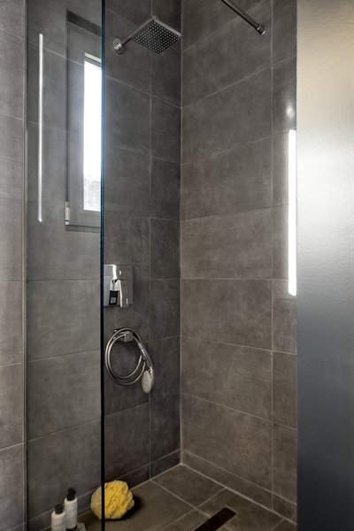 A clean, contemporary shower with a glass screen provides a quaint retreat.
