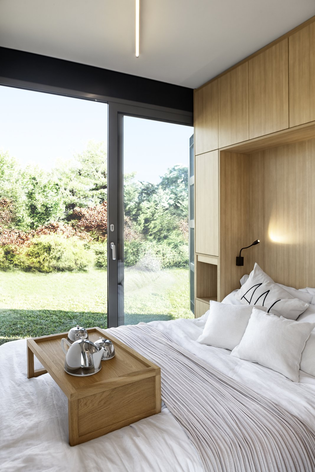 Bedroom, Ceiling Lighting, Storage, Bed, Light Hardwood Floor, and Wall Lighting Large windows draw daylight into the sleeping quarters, while providing beautiful views to the gardens.    Photo 6 of 10 in This Eco-Friendly Shipping Container Is the Ultimate Nomadic Dwelling