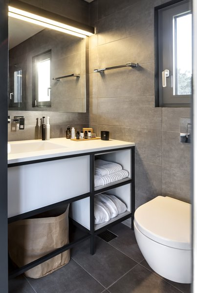 Bath, Porcelain Tile, Porcelain Tile, Wall, One Piece, and Drop In Small but efficient, the bathroom is completed with a vanity, storage, large mirror, and window.    Best Bath One Piece Porcelain Tile Photos from This Eco-Friendly Shipping Container Is the Ultimate Nomadic Dwelling