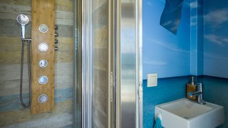The mobile hotel is complete with a full shower and multiple water pressures. Uniquely decorated with wood planks and a water motif, the shower feels like an ocean retreat.