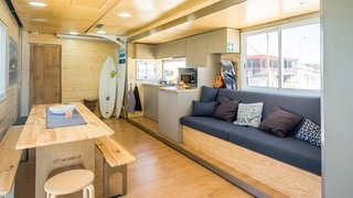 A full kitchen, lounge space, and dining area provide social quarters on the first floor of the bus.