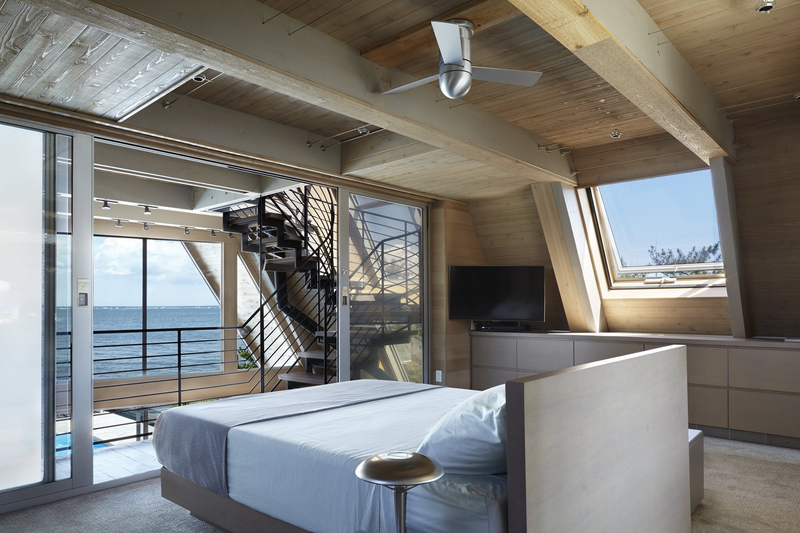 Loft bedroom with ceiling fan and ceiling track lighting.