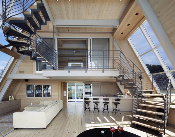 The open kitchen gently tucks under the upper floors and the wood and metal stair that delicately weaves its way upward. The large bay windows draw daylight in from both sides.
