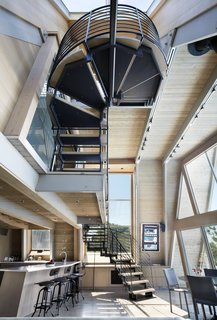The staircase is a sculptural solution composed of wood treads, steel supports, and a steel guardrail that winds its way upward.