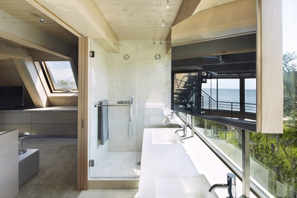 In the master bath, views do not diminish. A glass-enclosed shower and double vanity look onto the surrounding land. A post-mounted mirror provides vanity space while not blocking the views.