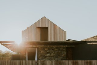 A simple composition in form, but intelligent in detail and execution, the peaked-roof dwelling is a stunning wood- and stone-clad living space.