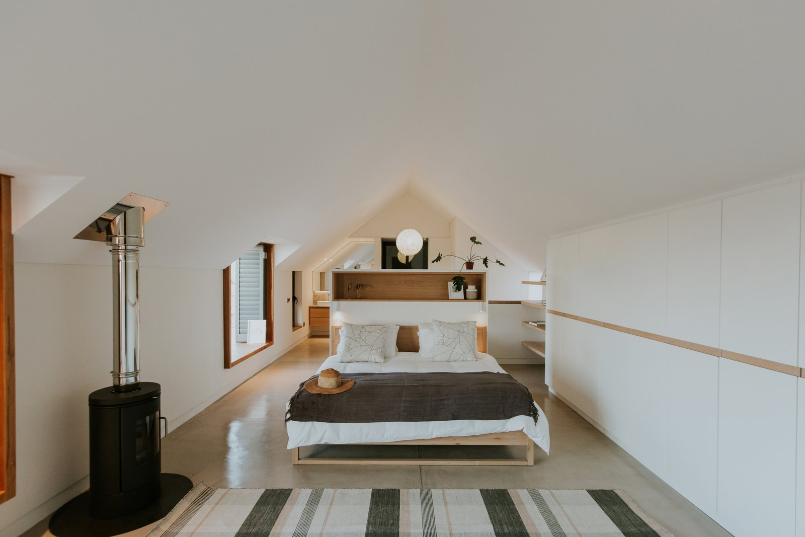 Bedroom, Concrete, Bed, Pendant, Rug, Shelves, and Table On the upper floor, the peaked roof form is revealed. A built-in headboard provides some separation between the functional spaces within the suite.  Best Bedroom Shelves Pendant Concrete Photos from An Inviting South African Cottage Embraces its Seaside Locale