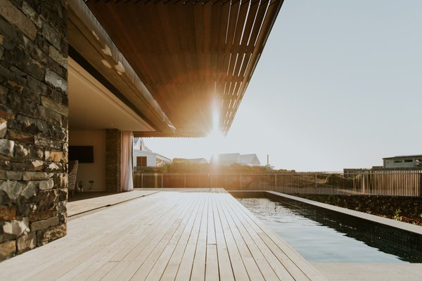 The wood canopy and the wood deck align in extension, framing views of the neighborhood beyond.