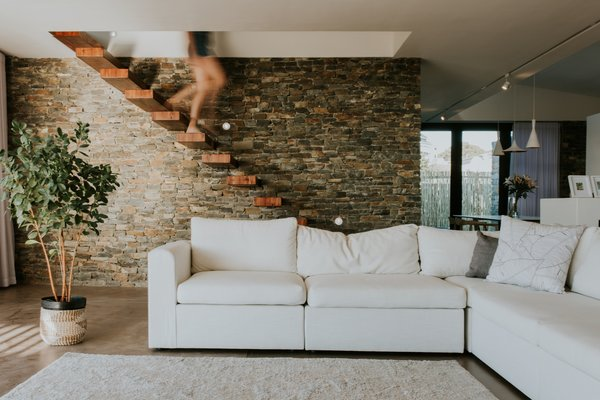 The floating wood stairs descend in front of a stone wall, which extends from the outside in.
